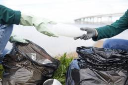 Manifesto REFIl. Close-up of volunteers cleaning nature from garbage they putting plastic bottles in rubbish bags