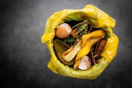Foto de comida e sobras no lixo, representando desperdício alimentar.