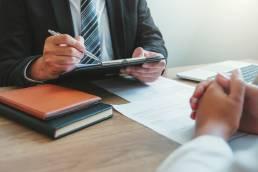 Homem consultor a informar cliente devedora a renogociar dívida e evitar incumprimento. Venda de Carteiras de Crédito.