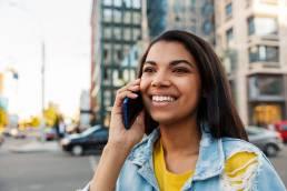 Mulher sorridente liga para linha telefónica do consumidor. A partir de 1 de novembro de 2021, existem novas regras para as linhas telefónicas dos fornecedores de bens e os prestadores de serviços.