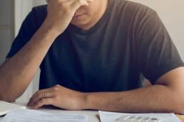 Fim da moratória pública. Homem adulto stressado com as prestações do crédito.