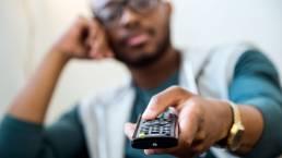 Retrato de jovem negro bonito assistindo tv em casa. Código da Publicidade,